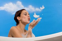 Young woman in bubble bath, blowing suds from hands, side view