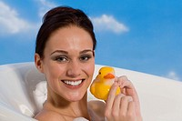 Young woman in bath holding rubber Duck, portrait