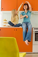 Mother and daughter 8_9 in the kitchen, mother balancing orange on head