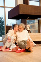 Mature couple sitting in front of fireplace