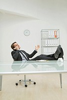 Businessman phoning, feet on desk