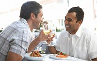 Two men sitting at outdoor cafe, toasting with wine