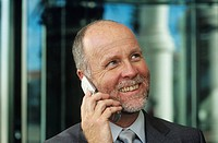 Mature businessman using mobile phone,smiling,close_up