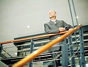 Mature businessman leaning on railing indoors,low angle view