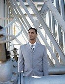 Business man at oil refinery in front of metal construction behind