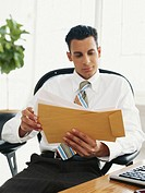 Businessman sitting in office looking at envelops