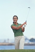 Young woman swinging golf club