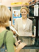 Female salesclerk demonstrating microwave to customer, smiling
