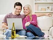 Couple on couch using laptop, smiling