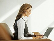 Businesswoman with hands free device sitting in armchair using laptop