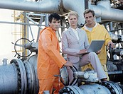 Group portrait of business woman and two oil refinery workers,woman holding laptop