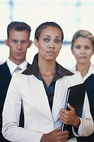 Businesswoman holding file standing with colleagues, portrait