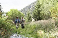 Two men walking though bushes wearing fishing gear