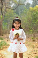 Little girl in white dress holding bouquet vertical
