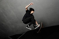 young man in mid air with skateboard