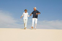 mature couple running down beach hand in hand