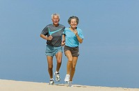 mature couple jogging together on sandy beach