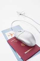 still life of computer mouse passport air ticket and toy airplane