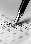 Tip of fountain pen marking date in calendar b&w close_up