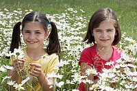 Two girls7_9 standing among flowers in meadow portrait