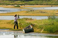 Woman photographing marsh