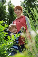 Mother embracing son 5-6 in garden portrait (thumbnail)