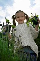 Girl 5_6 holding plants in garden portrait