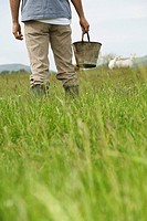 Man holding bucket in field mid section rear view