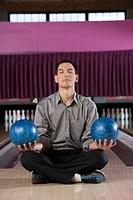 Man meditating with bowling balls in each hand