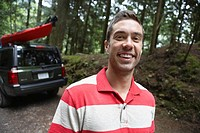 Man near car in forest smiling portrait