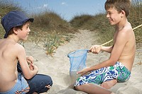 Two boys 6_11 in sand dunes playing with fishing net
