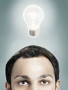 Illuminated lightbulb over man's head high section studio shot