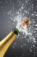 Champagne bottle popping cork close_up