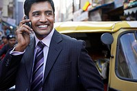 Business man using cell phone smiling