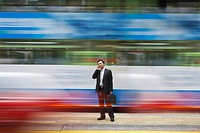 China Hong Kong business man using mobile phone standing on street long exposure