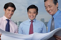 Three business men holding and looking at blueprints smiling