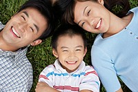 Couple with son 7_9 lying on grass portrait elevated view
