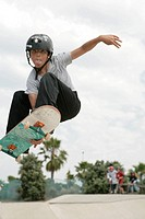 View of a teenage boy skateboarding.