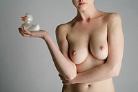 Cropped view of a nude woman holding a rubber duck