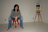 Asian man sitting in a room with easel and illustration