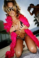 female posing for camera with red boa and sunglasses holding breasts