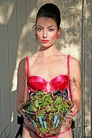 Woman in a bra, holding a bowl of lettuce