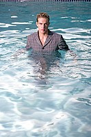 Man in a pool full clothed