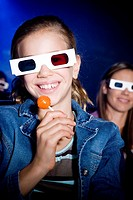 Girl with lollipop at the cinema watching a film through 3-D glasses