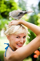 Beauty portrait of a woman in a tropical setting with a dove on her head