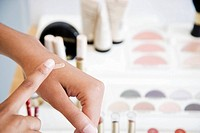 Woman testing foundation cream on her hand at the cosmetics counter