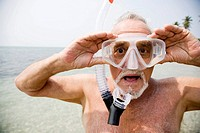 Senior man with snorkel gear at the beach