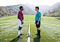 Opposing soccer players on field with ball