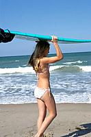 Girl on beach with surfboard