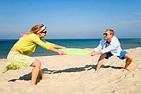 Couple fighting over bodyboard on beach